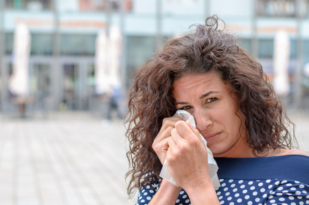 tearful: Tearful young woman wiping her eyes with a white handkerchief while looking at the camera with a melancholy expression