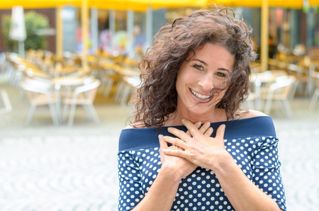 Grateful young woman with her hands to her heart standing outdoors in an town square smiling at the camera in gratitude
