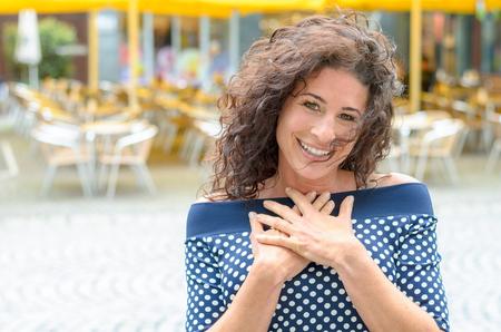 Grateful junge Frau mit ihren Händen ihr Herz im Freien in einer Stadt stehen Platz an der Kamera in Dankbarkeit lächelnd