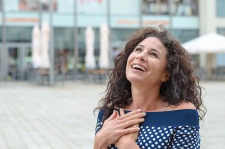 mujer joven agradecidos con sus manos al corazón pie al aire libre en una plaza de la ciudad que sonríe hasta el cielo en agradecimiento