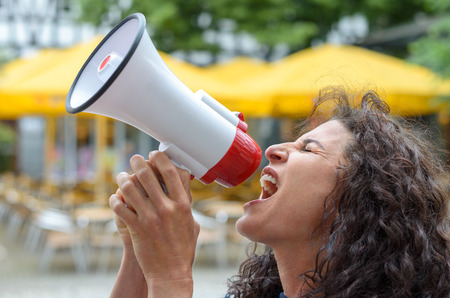 loud hailer: Angry young woman using a loud hailer or megaphone outdoors in an urban square during a protest or demonstration Stock Photo