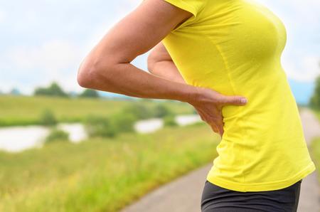Shapely fit junge Frau in einem bunten gelben Top Stretching mit ihren Händen auf dem Rücken, als sie eine Pause von ihrem täglichen Training oder Joggen entlang einer Landstraße nimmt, Nahaufnahme Körper Fokus Standard-Bild
