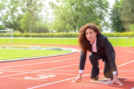 彼女の挑戦を満たすために、競争に勝つ準備として、スポーツ スタジアムでレース トラックでうずくまって開始位置の断固としたな女性実業家 写真素材