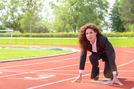 beat the competition: Determined businesswoman in the starting position crouching down on a race track in a sports stadium as she prepares to meet a challenge and beat the competition
