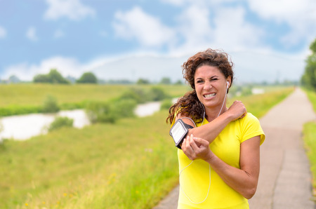 Young woman out jogging suffers a muscle injury standing holding her elbow while grimacing in pain on a rural road, close up upper body view Stock Photo