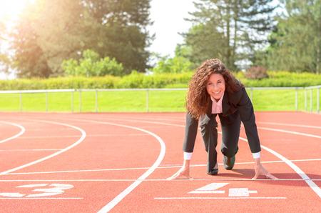 Lächelnd zuversichtlich Geschäftsfrau in der Starterposition auf einer Rennstrecke in einem Sportstadion in ihrem stilvollen Business-Anzug in einem konzeptionellen Bild
