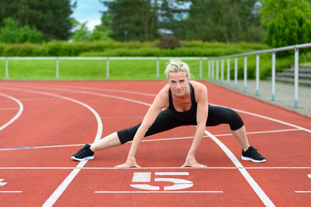 supple: Single athletic mature woman in black jump suit doing straddle stretches on red racing track