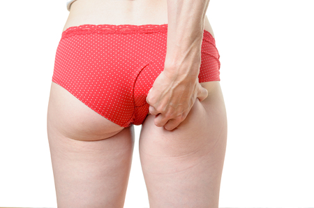 grabbing back: Young woman wearing sexy red panties standing with her back t o the camera grabbing excess fat on her buttocks or bum in her hand, close up torso view isolated on white