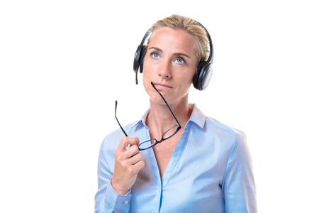 short haired: Serious gorgeous short haired blond woman with telephone headset holding eyeglasses near mouth while looking upward over white background Stock Photo