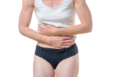 underpants: Close up of unidentifiable single woman in black underpants and white shirt holding stomach in pain for digestive disorder concept Stock Photo