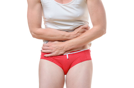 unidentifiable: Close up of unidentifiable single woman in red underpants and white shirt pressing stomach with hands for digestive disorder or pain concept Stock Photo