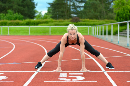 straddle: Single athletic mature woman in black jump suit doing straddle stretches on red racing track