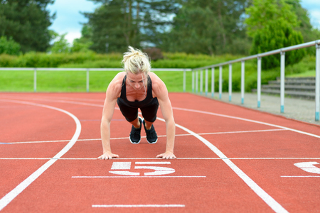 lithe: Single athletic mature woman in black jump suit calf leg muscle stretching exercises on red racing track outdoors
