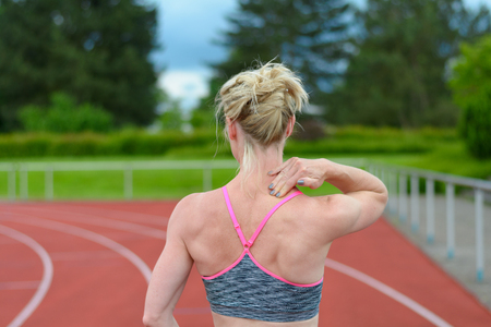 upper half: Rear view of athletic female sprinter massaging her own neck at race track with trees in background Stock Photo
