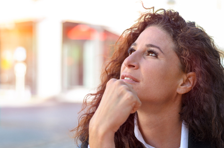 wistful: Thoughtful gorgeous young woman sitting daydreaming with her chin on her hands staring into the air with a wistful expression Stock Photo