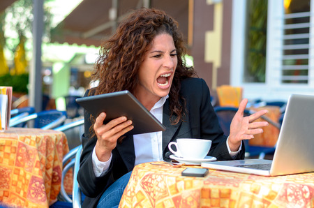 Angry frustrated young businesswoman yelling at her laptop computer as she sits at an outdoor restaurant table enjoying coffee