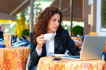 Dedicated serious young businesswoman sitting drinking coffee at an outdoor restaurant while working on her laptop computer Фото со стока