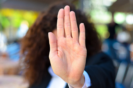 authoritative: Woman giving the halt or stop sign holding up her palm in an authoritative manner indicating she has had enough, no access or halt immediately
