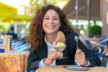 beaming: Attractive young woman with a large ice-cream sundae in a metal bowl sitting at a table at an outdoor cafe beaming at the camera in anticipation Stock Photo