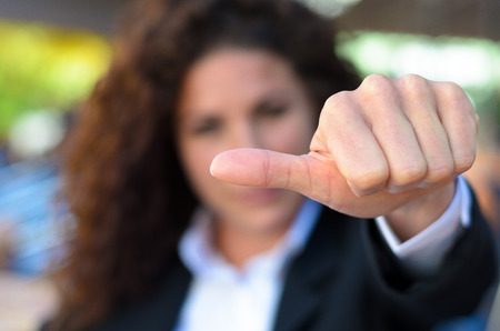 abstention: Woman abstaining from voting holding her thumb to the side to show her uncertainty, disinterest or abstention Stock Photo