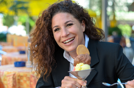 icecream sundae: Attractive young woman with a large ice-cream sundae in a metal bowl sitting at a table at an outdoor cafe