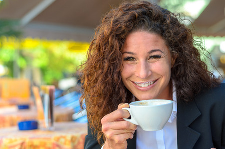 beaming: Exultant young woman enjoying a cup of coffee as she sits at an open-air cafe looking over the cup at the camera with a wide beaming joyful smile