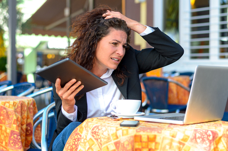 perplexed: Perplexed stressed young businesswoman holding her hand to her hair and frowning at her laptop computer as she sits at a restaurant table outdoors