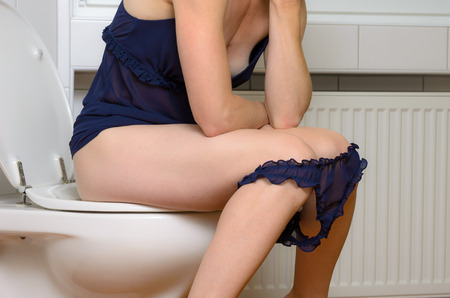 defecation: Young woman in underwear sitting on a toilet with her blue panties around her knees in a close up side view of her body Stock Photo