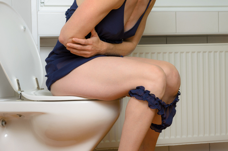 defecation: Woman with a stomach ache sitting on a toilet clutching her midriff with her arms with her blue panties around her knees, close up body view