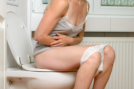 whitw: Woman with a stomach ache sitting on a toilet clutching her midriff with her arms with her whitw panties around her knees, close up body view Stock Photo