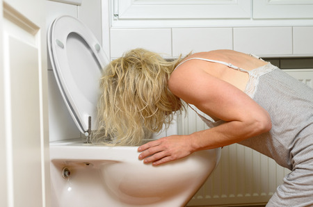drunkenness: Blond woman in a grey dress kneeling down vomiting into a toilet conceptual of an illness or drunkenness after a party Stock Photo