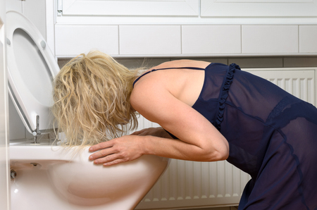 drunkenness: Blond woman in a black dress kneeling down vomiting into a toilet conceptual of an illness or drunkenness after a party