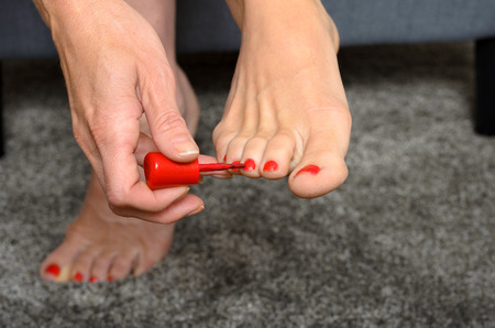 toenails: Woman applying red nail varnish to her toenails using an applicator brush,close up view on her hand and bare feet