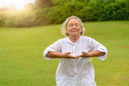 ホワイトの美しいシニア女性の単一コピー スペースと緑の草の閉じた目と外呼吸の練習長袖ブラウス ロールアップ