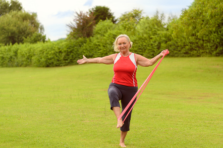arm bands: Fit senior woman in red sleeveless shirt using elastic resistance bands with leg and arm outside in field of green grass with copy space Stock Photo