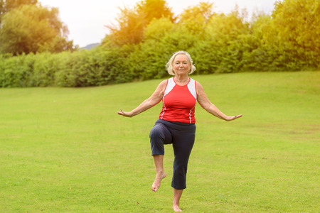 Calm barefoot athletic senior woman performing yoga balancing exercises on one leg at outdoor park with green grass and copy space Foto de archivo
