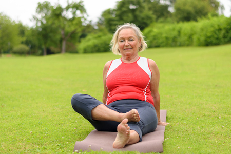 Grinning senior woman sitting on yoga mat outdoors in park with wide open field of green turf grass and copy space