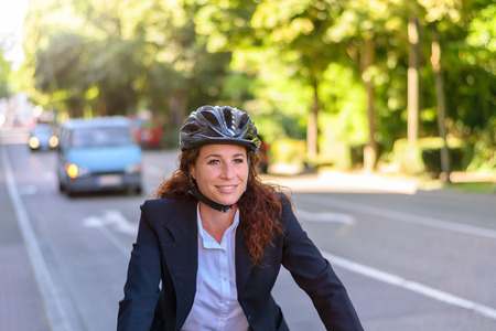 Attractive professional woman wearing a safety helmet cycling to work along an urban street with traffic, close up upper body view Banco de Imagens