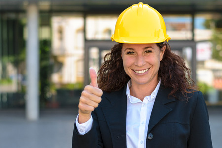 structural engineers: Happy successful young female architect or structural engineer wearing a hardhat and giving the camera a thumbs up gesture