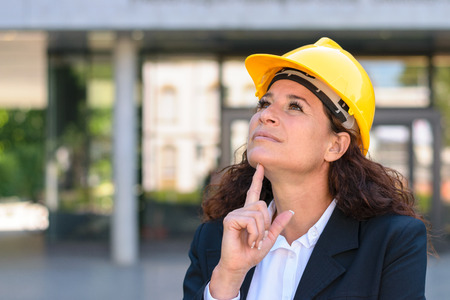 structural engineers: Thoughtful young female architect or building inspector standing staring up into the air with a pensive expression in a yellow hardhat Stock Photo