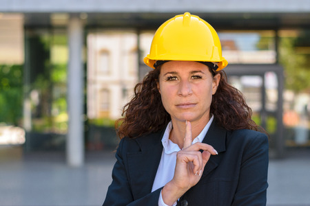 speculate: Thoughtful young professional woman architect wearing a hardhat standing in front of an urban building staring intently at the camera