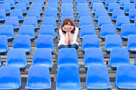 spectator: Glum woman sitting in empty rows of blue spectator seating in an auditorium or stadium with a bored expression and her chin on her hands