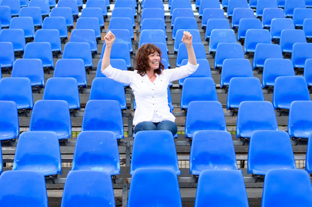 spectator: Lone female fan or spectator sitting cheering in amongst rows of empty blue seats in an auditorium or stadium