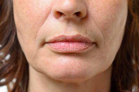 Primo piano sulla bocca di una donna di mezza età bruna con la bocca chiusa e un'espressione seria Archivio Fotografico - 59848626