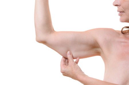 ageing: Middle-aged woman grasping her underarm flesh between her fingers showing the slackening of the tissue due to ageing, isolated on white