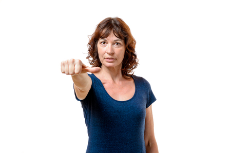 neutrality: Attractive middle-aged woman abstaining from voting indicating her indifference or neutrality with her thumb to the side, isolated on white