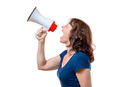 defiance: Middle-aged woman yelling into a megaphone or bullhorn at a rally or protest registering her grievances in defiance, side view isolated on white Stock Photo