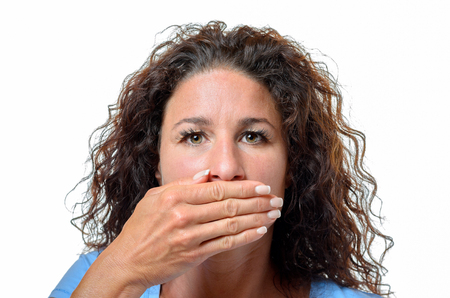 circumspect: Serious young woman with long curly hair covering her mouth with her hand in a Speak No Evil concept, head shot isolated on white Stock Photo