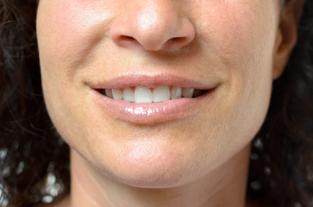 smile close up: Young woman with a lovely sensual smile and slightly parted lips showing her teeth, close up detail of her mouth