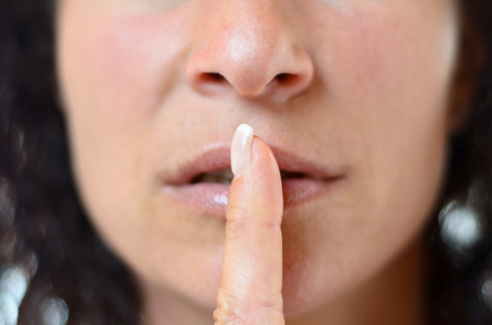 shushing: Woman making a shushing gesture for silence holding her finger to her lips, close up detail of her mouth